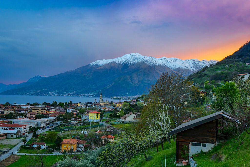 Domaso mit feurigem Sonnenuntergang hinter schneebedeckten Bergen - Comer See - Lombardei, Italien