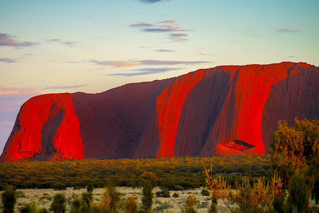 Uluru - Faszinierende Farbenspiele tauchen den Ayers Rock in leuchtendes Purpurrot beim Sonnenaufgang - Northern Territory