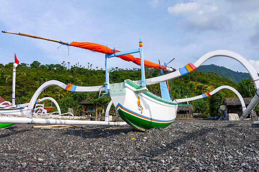 Dunkler Kiesstrand und typische Fischerboote bei Amed Bali - Indonesien
