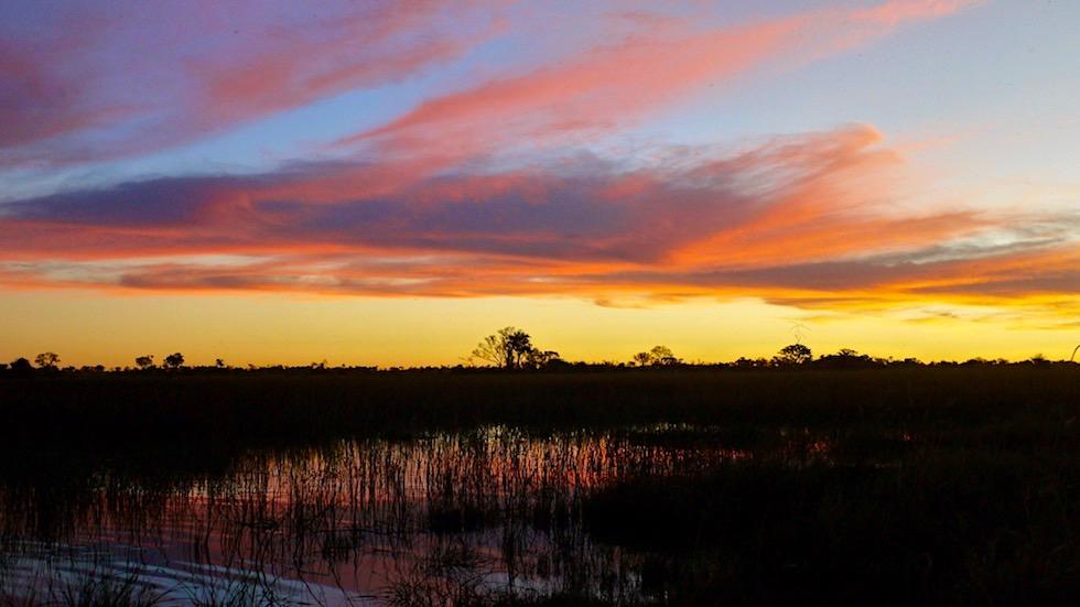 Zauberhafte, leuchtende, friedliche Sonnenuntergänge inmitten des Okavango Deltas - Botswana