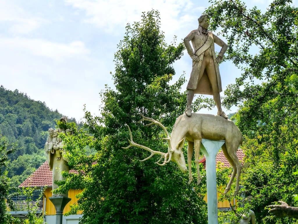 Peter Lenk Skulpturengarten - Herzog Carl Eugen auf einem toten Hirsch ist Teil der Hölderlin im Kreisverkehr Skulpturen Gruppe in Laufen am Neckar - Baden-Württemberg