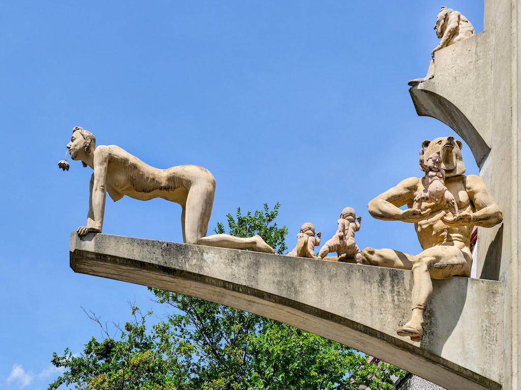 Paradiesbaum - Singener Wappenbär & Vorzimmerdame, die Blumenkönigin werden möchte - Peter Lenk Skulptur - Singen, Baden-Württemberg